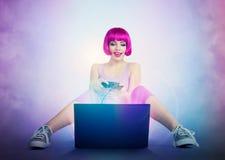 La giovane donna con la leva di comando si siede sul pavimento davanti ad un computer portatile Giochi del Gamer Fotografie Stock Libere da Diritti