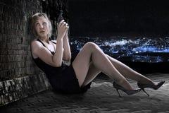 La giovane donna con la pistola su un tetto. Fotografia Stock Libera da Diritti