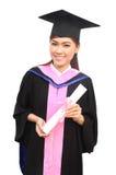 Donna con la protezione e l'abito di graduazione con il braccio alzato Immagini Stock