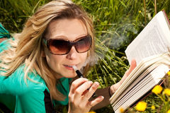 La giovane donna con la sigaretta elettrica ha letto il libro Fotografie Stock Libere da Diritti