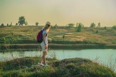 La giovane donna con lo zaino rosa sta stando sulla fine blu del fondo delle cave del gesso su nel tempo del tramonto immagini stock