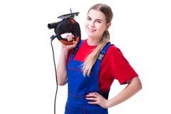 La giovane donna con la sega elettrica isolata su bianco Immagini Stock