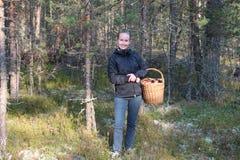 La giovane donna con un canestro dei porcini si espande rapidamente nella foresta Immagini Stock