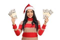 La giovane donna con un cappello di Natale con soldi impacchetta Fotografia Stock