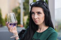 La giovane donna con un vetro del cocktail viola sopra si siede sul terrazzo dell'estate del ristorante fotografia stock libera da diritti