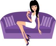 La giovane donna con un vetro di vino si siede su un sofà illustrazione vettoriale