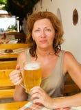 La giovane donna con una birra Fotografie Stock