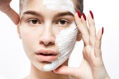La giovane donna con una maschera cosmetica bianca su una metà del suo fronte tiene le sue mani al suo fronte sui precedenti bia immagini stock
