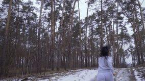 La giovane donna controlla il tempo durante il funzionamento nella foresta stock footage