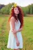 La giovane donna in corona e vestito da short posa sul prato a Fotografia Stock Libera da Diritti