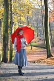 La giovane donna costa con un ombrello rosso nel parco di autunno Fotografia Stock Libera da Diritti