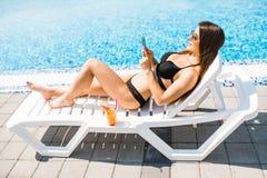 La giovane donna in costume da bagno che si rilassa con il cocktail sulle chaise longue ed utilizza il suo telefono per mandare u immagini stock