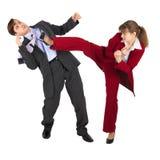 La giovane donna dà dei calci all'uomo in vestito di affari Fotografia Stock