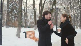 La giovane donna dà un naso sparay all'uomo di starnuto nel parco dell'inverno archivi video