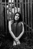 La giovane donna dai capelli lunghi attraente in jeans si siede vicino ad un recinto di legno Fotografia Stock