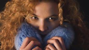 La giovane donna dai capelli riccia nasconde il suo fronte in un collare della pelliccia archivi video