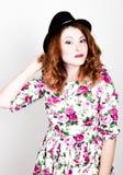 La giovane donna dai capelli rossi alla moda con capelli ricci ed il fronte grazioso tiene un black hat esprime le emozioni diffe Fotografia Stock