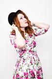 La giovane donna dai capelli rossi alla moda con capelli ricci ed il fronte grazioso tiene un black hat esprime le emozioni diffe Immagine Stock