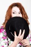La giovane donna dai capelli rossi alla moda con capelli ricci ed il fronte grazioso tiene un black hat esprime le emozioni diffe Immagine Stock Libera da Diritti