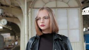 La giovane donna dai capelli rossi attraente con breve taglio di capelli, vetri d'uso ed il bomber nero sta stando a bello stock footage