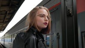 La giovane donna dai capelli rossi attraente con breve taglio di capelli, vetri d'uso ed il bomber nero sta stando a bello video d archivio