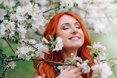 La giovane donna dai capelli rossi felice sta nel meleto sbocciante, fine su fotografie stock libere da diritti