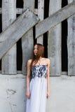 La giovane donna dai capelli rossi in vestito floreale vicino ha abbandonato la costruzione Fotografia Stock