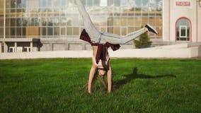La giovane donna dei pantaloni a vita bassa con teme girare i cartwheels in un parco durante il giorno di estate soleggiato lumin video d archivio
