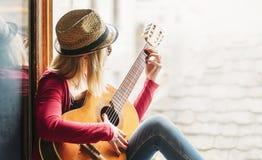 La giovane donna dei pantaloni a vita bassa gioca la chitarra Immagini Stock