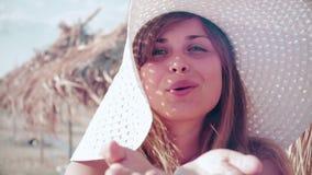 La giovane donna del movimento lento in un cappello invia un bacio dell'aria lei cara sulla spiaggia archivi video