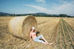 La giovane donna dell'agricoltore è sedentesi e pendente al mucchio di fieno durante Fotografia Stock