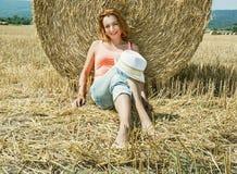La giovane donna dell'agricoltore è sedentesi e pendente al mucchio di fieno durante Fotografie Stock