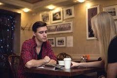 La giovane donna dell'uomo dei pantaloni a vita bassa di due amici sta sedendo dentro Immagine Stock