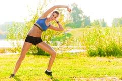 La giovane donna della disposizione esegue l'allungamento degli esercizi nel parco Immagini Stock