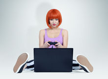 La giovane donna della testarossa con la leva di comando si siede sul pavimento davanti ad un computer portatile Giochi del Gamer Immagine Stock Libera da Diritti