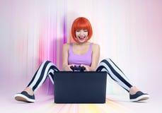 La giovane donna della testarossa con la leva di comando si siede sul pavimento multicolore davanti ad un computer portatile Gioc Immagini Stock Libere da Diritti