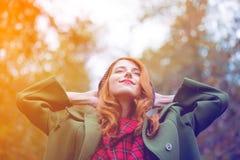 La giovane donna della testarossa in vestito rosso con il cappotto verde all'autunno si batte immagini stock libere da diritti