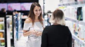 La giovane donna in deposito sceglie lo sciampo, venditore che il consulente parla dei cosmetici, movimento lento