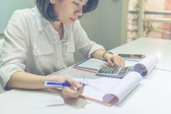 La giovane donna di affari asiatica calcola le vendite sul calcolatore fotografie stock