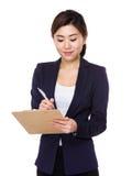 La giovane donna di affari asiatica prende nota sulla lavagna per appunti fotografia stock libera da diritti