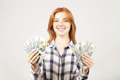 La giovane donna di affari attraente che posa con il mazzo di USD incassa le mani che mostrano le emozioni positive e l'espressio fotografie stock