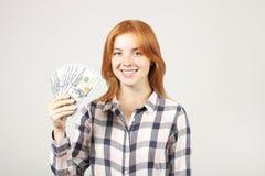 La giovane donna di affari attraente che posa con il mazzo di USD incassa le mani che mostrano le emozioni positive e l'espressio immagine stock