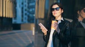 La giovane donna di affari attraente con la tazza di caffè sta utilizzando lo Smart Phone nella città con gli edifici per uffici stock footage
