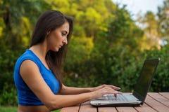 La giovane donna di affari attraente ha messo a fuoco sul suo lavoro che esamina lo schermo del computer portatile che si siede n Immagini Stock Libere da Diritti