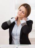 La giovane donna di affari attraente soffre da dolore al collo Immagine Stock