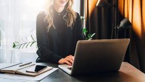 La giovane donna di affari in camicia nera sta sedendosi alla tavola, lavorante al computer Vicino è il taccuino, smartphone alli Immagini Stock