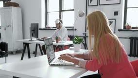 La giovane donna di affari che lavora allo scrittorio comune in pantaloni a vita bassa d'avanguardia inizia sull'ufficio facendo  stock footage