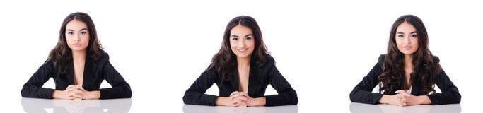 La giovane donna di affari che si siede allo scrittorio sul bianco Immagine Stock