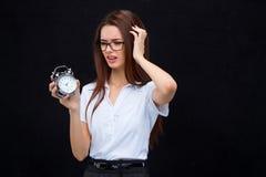 La giovane donna di affari con la sveglia su fondo nero Fotografia Stock