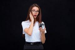 La giovane donna di affari con la sveglia su fondo nero Fotografie Stock Libere da Diritti